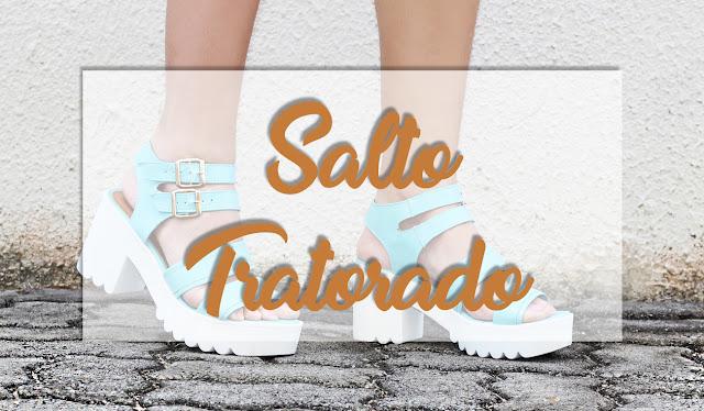 Pés calçados com sandália branca e azul de solado com salto tratora e escrito por cima da imagem: salto tratorado
