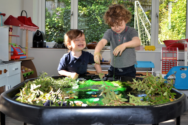 happy children playing with Pond Tuff tray with frogs and frog spawn