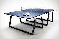 Siyah ve lacivert renkli bir masa tenisi masası ve üzerinde bırakılmış raketler