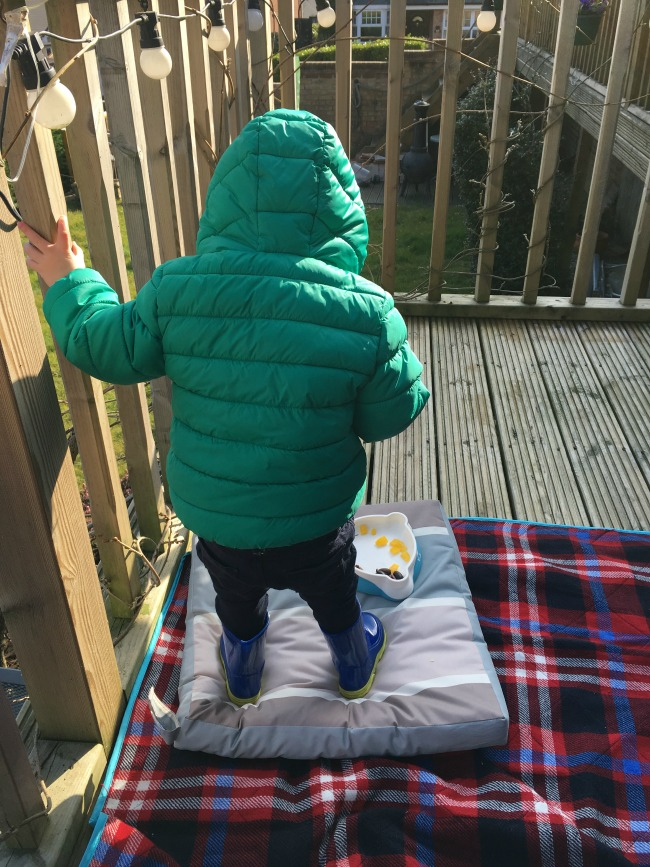 Planting, Postman Pat and a Picnic. toddler standing on decking with blanket and cushion