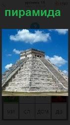 Под голубым небом с облаками стоит пирамида, выполненная со ступеньками  белым камнем