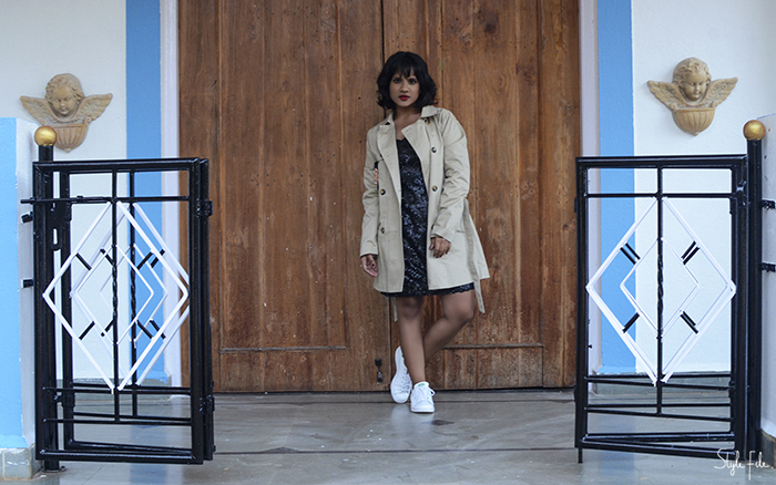 Image of woman wearing winter fashion clothing with a Zara beige trench coat, H&M black sequin dress and white Adidas Originals Stan Smith sneakers with red lipstick, burgundy nail polish and wavy bob hairstyle