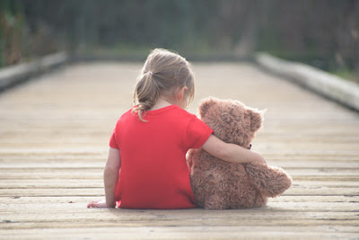 sad child sitting with teddy bear