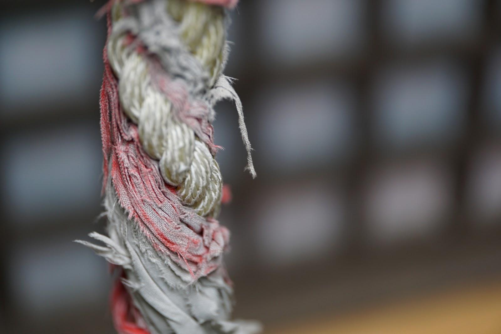 神社の赤と白で縒られた古びた鈴緒