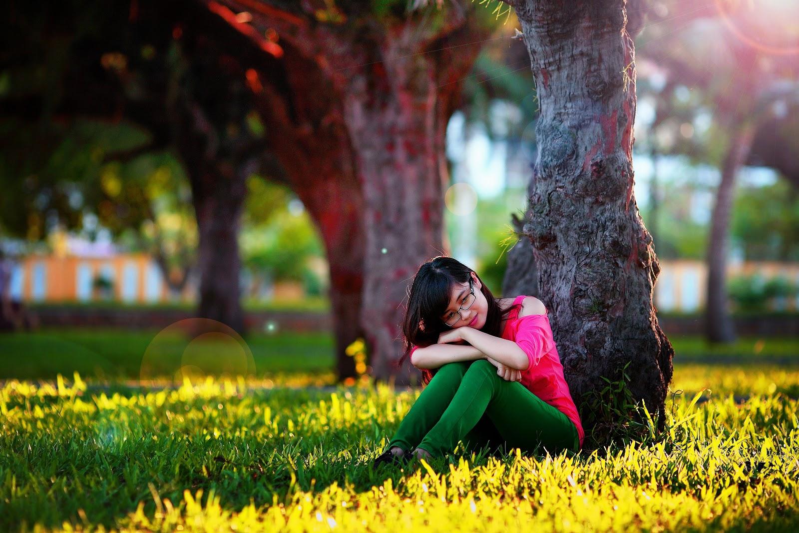 草地に座って温和な表情を浮かべながら考える女性