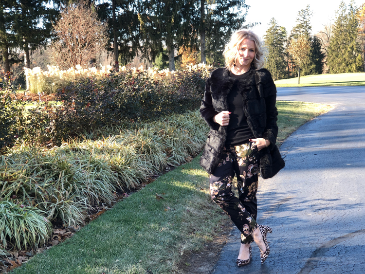 black fur coat with floral pants and leopard heels