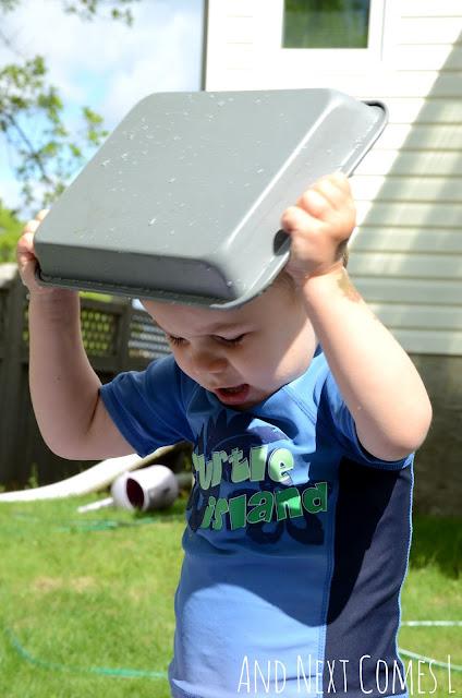Young preschooler putting a metal pan on his head