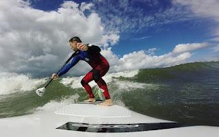 SUP surfer na fali w Polsce