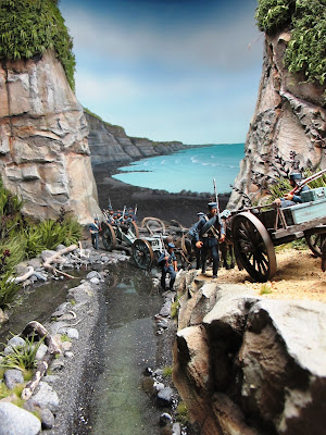 Diorama of 19th-century soldiers crossing a creek and mounting a track by the sea.