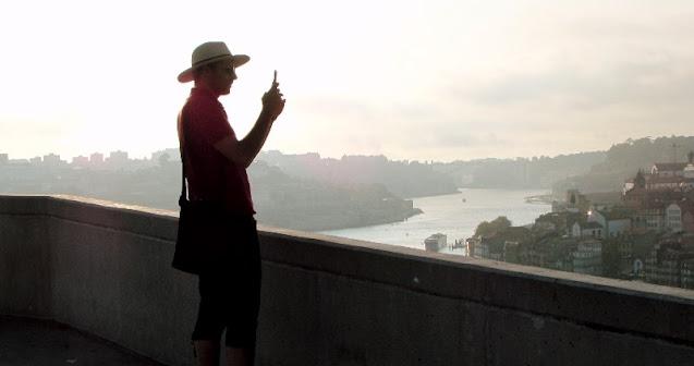 Homem de chapéu fazendo uma foto a partir do Jardim do Morro
