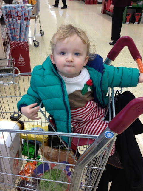 Toddler sat in shopping trolley wearing Christmas pudding suit