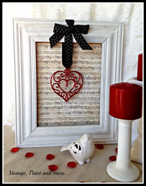 A vintage thrifted frame with vintage sheet music and a Christmas ornament make a cute Valentine decor