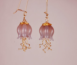 carved bluish grey moonstone pods with dangling 18k wires and 22k gold caps