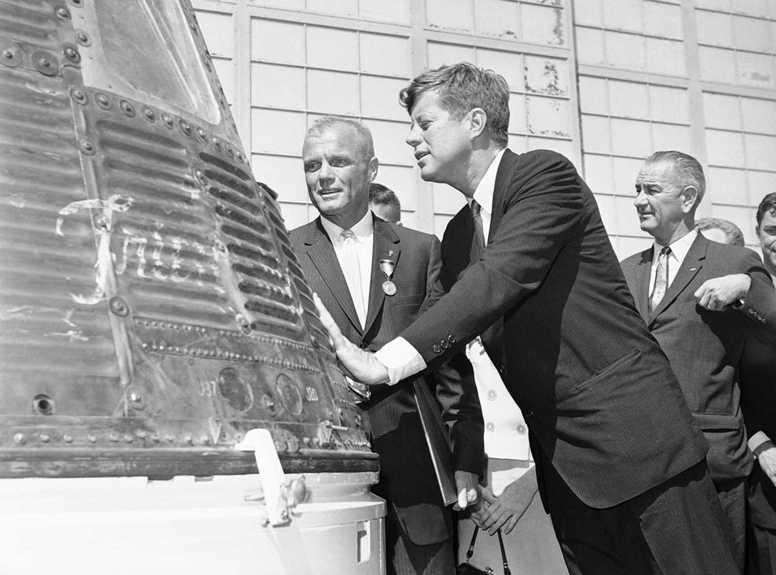 Astronaut John Glenn and President John Kennedy inspect the Friendship 7, the Mercury capsule which Glenn rode in orbit. Kennedy presented the Distinguished Service Medal to Glenn on February 23, 1962 at Cape Canaveral, Florida.