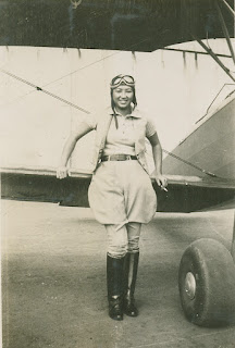 Hazel Ying Lee standing in front of an airplane wing wearing flying garb.