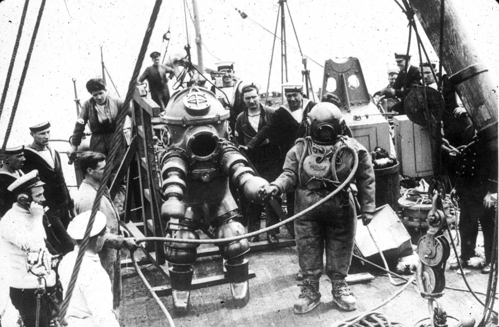 Two divers, one wearing the Tritonia ADS and the other standard diving dress, preparing to explore the wreck of the RMS Lusitania, 1935.