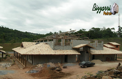 Fachada dos fundos da construção rústica na parte da execução do madeiramento com eucalipto tratado em fase final já iniciando a execução da cobertura do telhado com telhas de barro colonial mesclada.