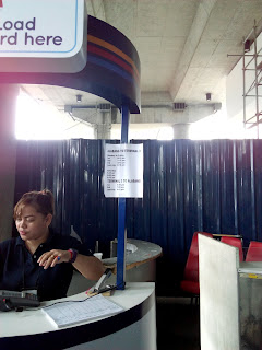 girl in a kiosk in the NAIA airport going to baclaran or MRT station