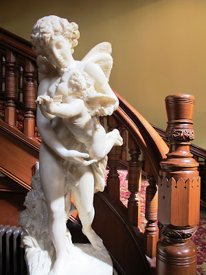 Large statue at the foot of a curved staircase.