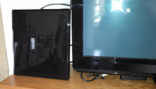 Black rectangular antenna next to TV