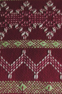 closeup of patterns formed by stitching on a even weave background fabric
