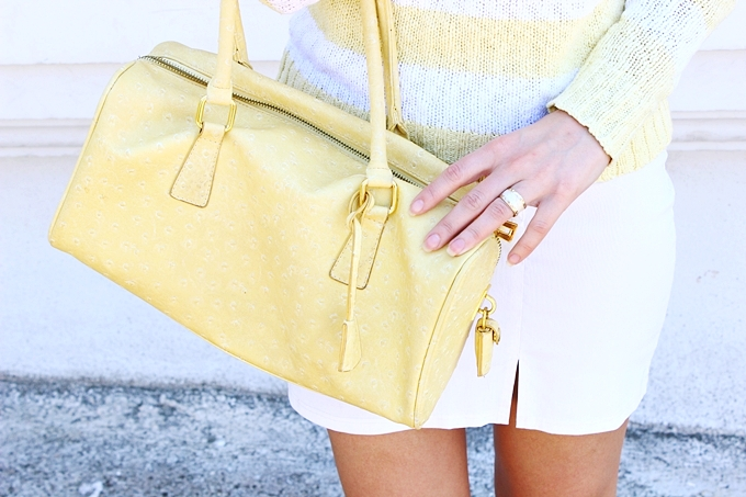 Yellow purse white skirt.