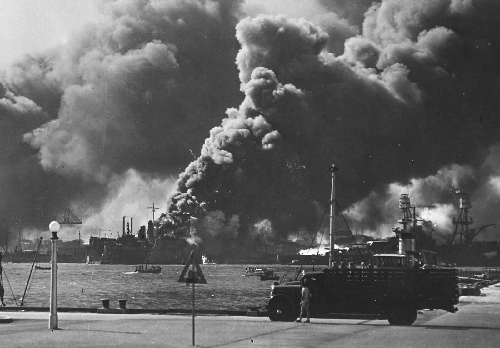 The USS Shaw burns in Pearl Harbor. Japanese bombers hit the forward portion of the ship with three bombs. The resulting fires proved uncontrollable, and Shaw was ordered abandoned. Soon after, her forward ammunition magazines detonated in a spectacular blast, completely removing her bow.
