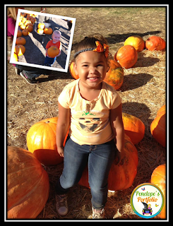 A cute little girl sitting on a large pumpkin, with other pumpkins surrounding her