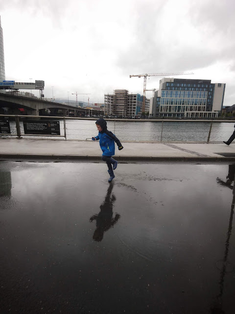 Boy (Dylan) running through puddles in the rain with a river and buildings in the background. My Sunday Photo - Us Two Plus You
