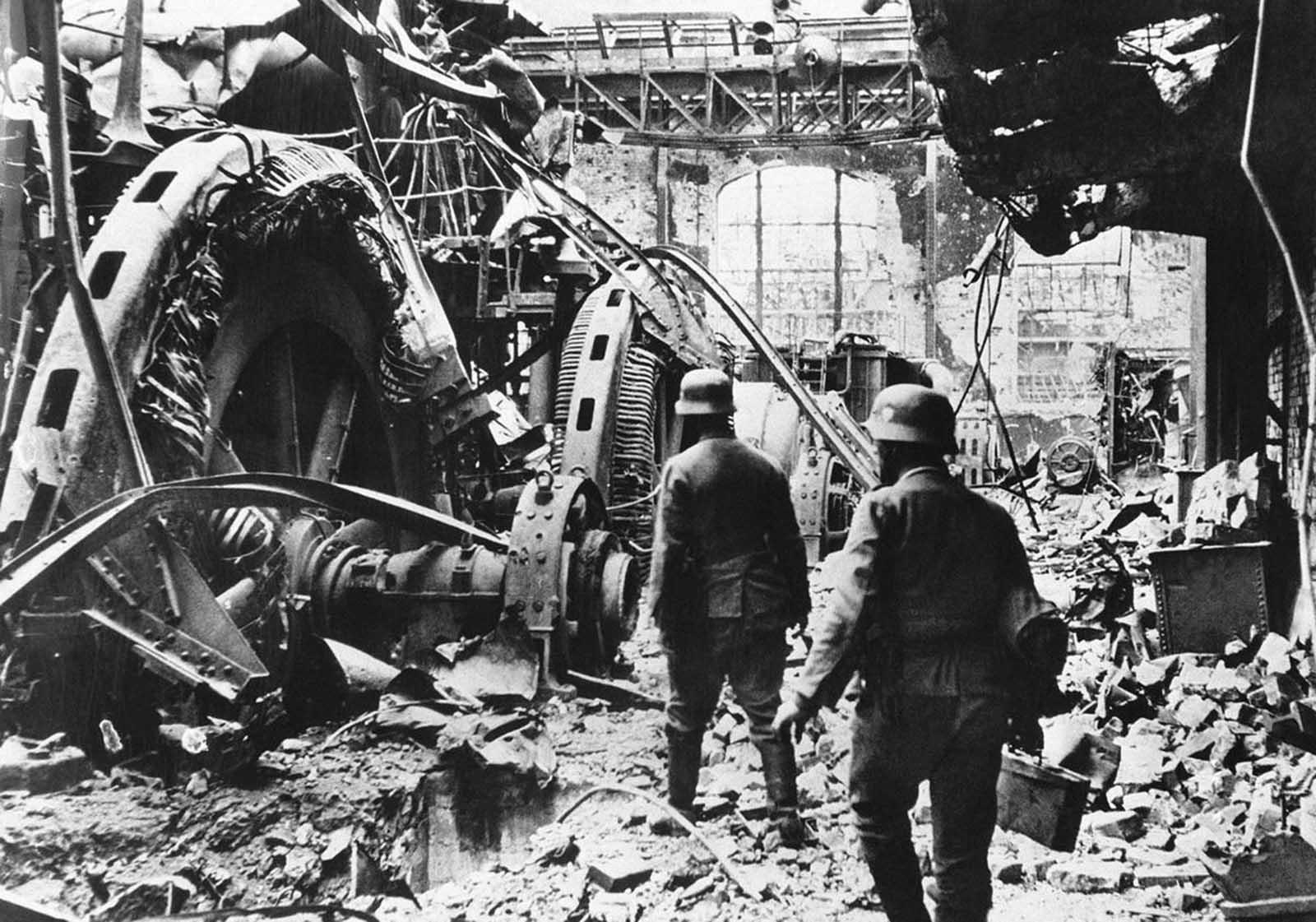 German troops pass through a wrecked generating station in the factory district of Stalingrad, on December 28, 1942.