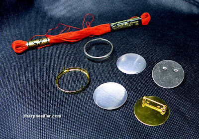 A selection of metal pin settings in gold and silver used for mounting wearable embroidery projects