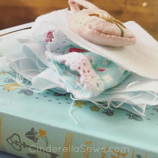 Tiny doll clothes I'm currently stitching for my new pattern release sitting on pretty books
