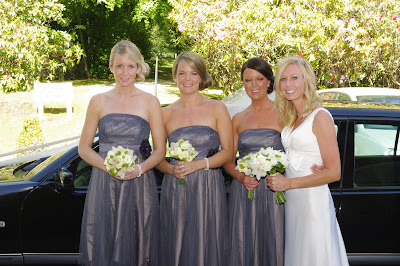Bride, bridesmaids and maid of honour in front of wedding car on the morning of her wedding