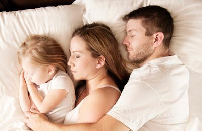 Padre madre e hija durmiendo juntos