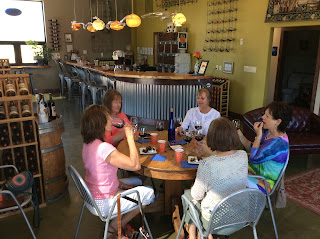 Five ladies wine tasting around a round table.