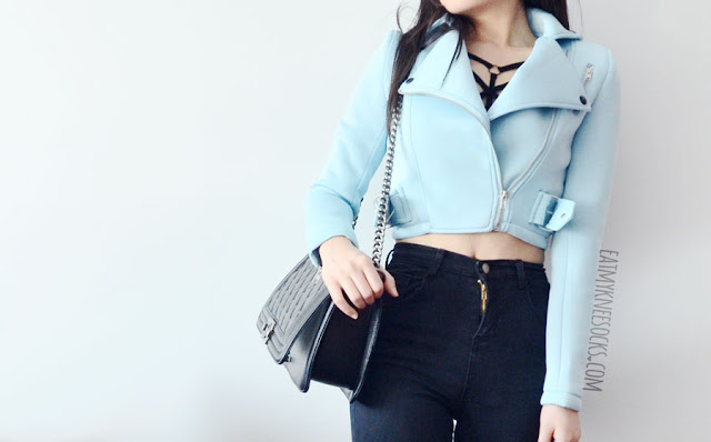 A classy-chic outfit featuring BagInc's Ingrid quilted black medium leather purse, modeled with a pastel blue cropped moto jacket, Free People strappy bralette, high-waisted distressed ripped skinny jeans, and blue velvet high-heeled booties.