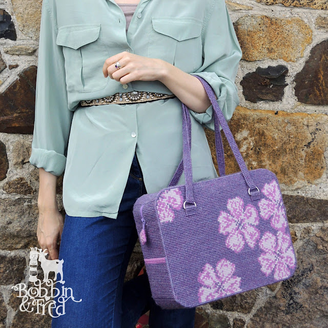 Chic woman leaning against wall modelling craft project bag