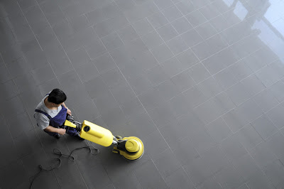 Janitor Using Yellow Floor Equipment to Clean Tile Floor