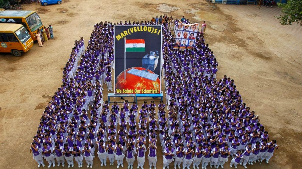 Indian school children pose for photographs with a poster of Mars Orbiter Mission satellite as they celebrate its success in Chennai, India, Wednesday, Sept. 24, 2014. India triumphed in its first interplanetary mission, placing a satellite into orbit around Mars on Wednesday and catapulting the country into an elite club of deep-space explorers. (AP Photo/Arun Sankar K)