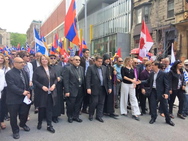 Ελληνικές σημαίες ανεμίζουν στην πορεία. Στην κεφαλή της ο δήμαρχος Μόντρεαλ Ντενί Κοντέρ. Δεξιότερα διακρίνονται η υπουργός Πολιτιστικής Κληρονομιάς του Καναδά Μελανί Ζολί και η αντιδήμαρχος Μόντρεαλ Μαίρη Ντέρος