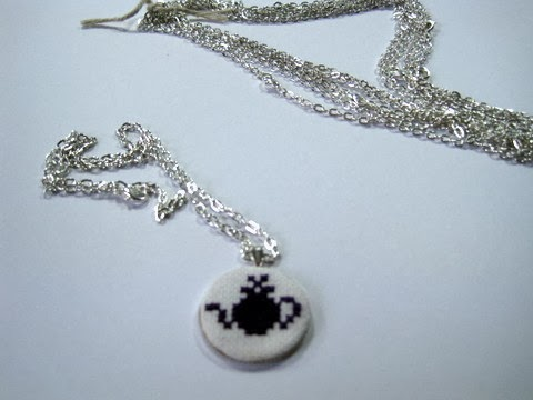 Cross stitched teapot necklace stitched and finished into a necklace with a silver chain