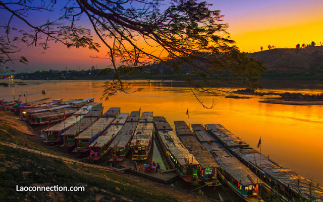 Boats dock as the sun sets over Huayxai