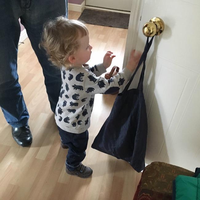 toddler reaching up to door handle
