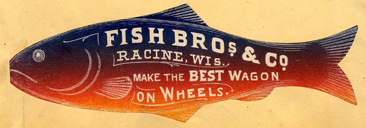 """Fish Bros. & Co., Racine WI, Make the Best Wagon on Wheels"" reads the white print on this graduated tint dark blue (top) to orange and yellow fish (belly), facing left"