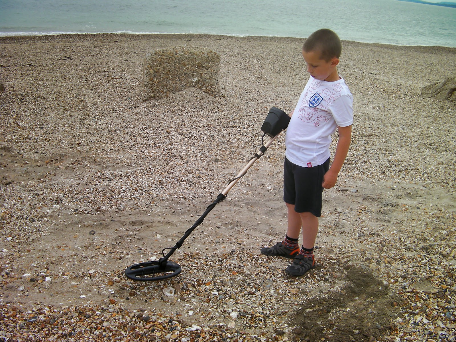 fisher F4 metal detector on shingle beach with world war 2 anti-amphibious tank defence blocks
