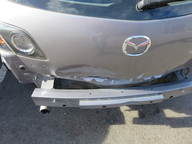 Dented tailgate & bumper on Mazda 3 before auto body repairs & paint at Almost Everything Auto Body