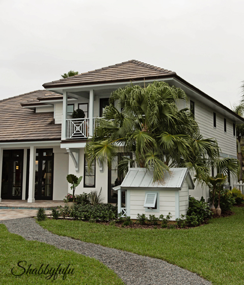 An exterior view of the HGTV Dream Home 2016 - landscaping, palm trees, and a dog house.