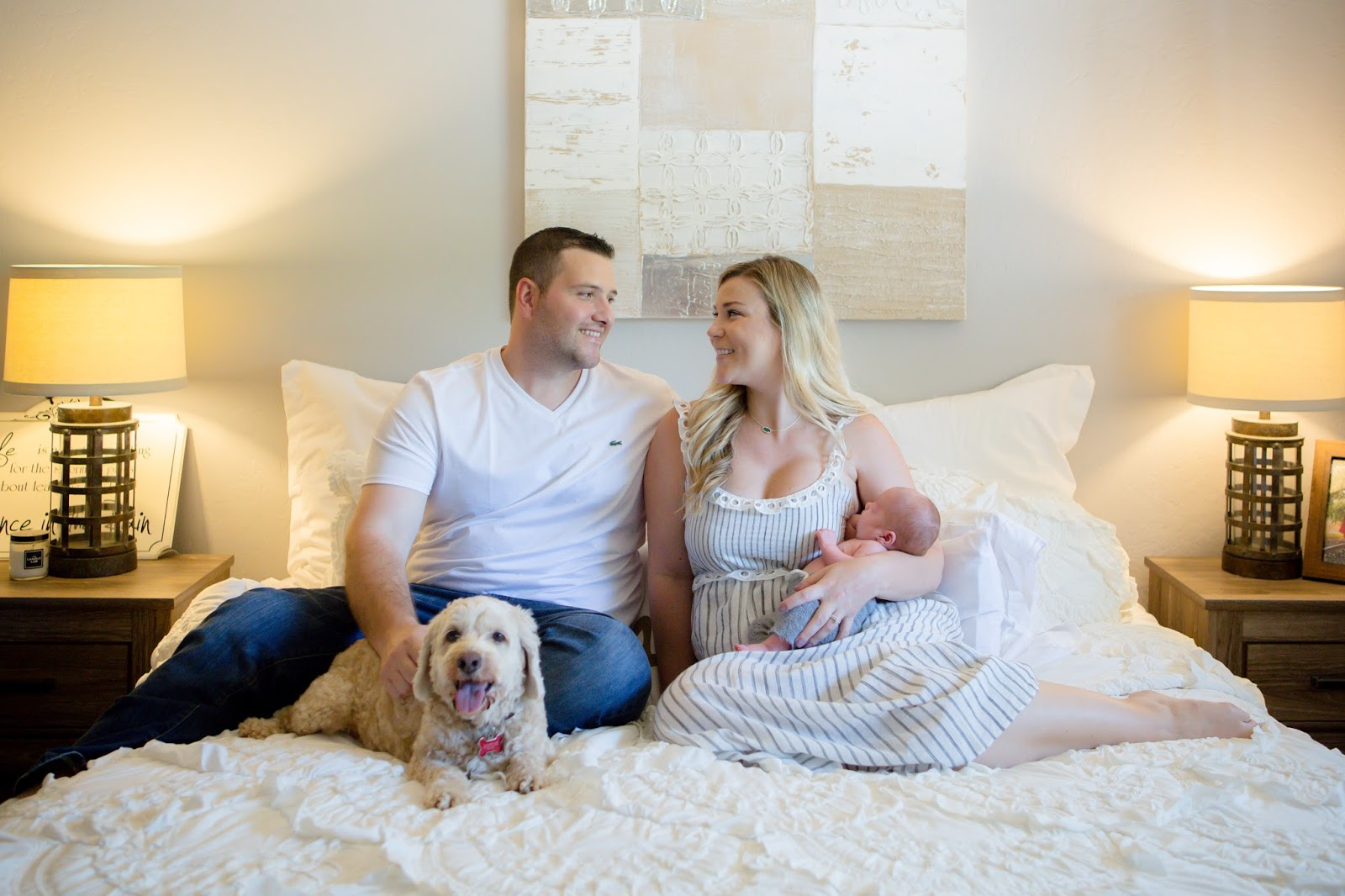 mom, dad, baby and dog on bed