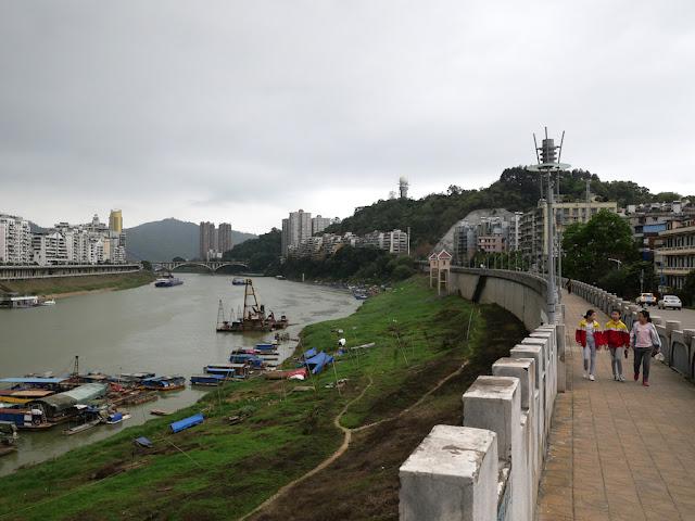 three elementary school students walking on a wall bordering the Gui River (桂江) in Wuzhou (梧州)