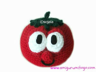 red crocheted tomato with green stem